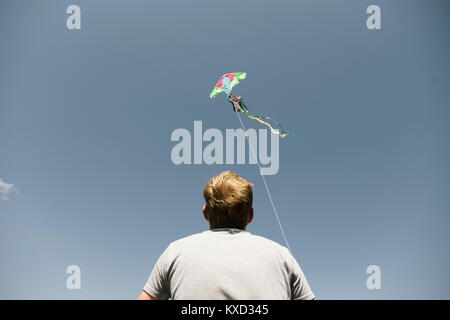 Low angle view of man flying kite against sky - Stock Photo