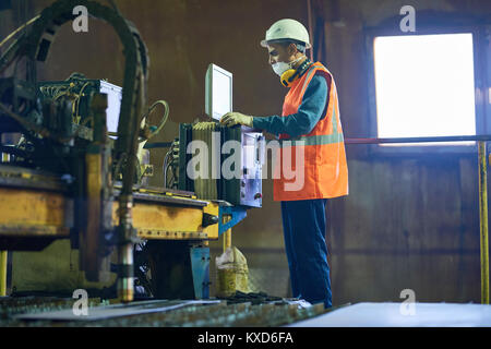 Machine Operator Concentrated on Work - Stock Photo