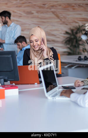 Beautiful phone operator Arab woman working in modern startup office - Stock Photo