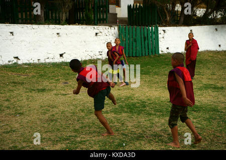 Buddhist monk boys playing soccer with rolled up robes, Dzong Paro, town Paro, Bhutan - Stock Photo