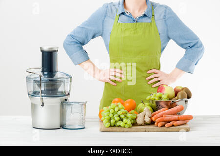 Anonymous woman wearing an apron, ready to start preparing healthy fruit juice using modern electric juicer, healthy - Stock Photo