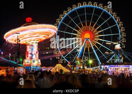 Chain carousel and Ferris wheel at night, Oktoberfest, Theresienwiese, Munich, Upper Bavaria, Germany - Stock Photo
