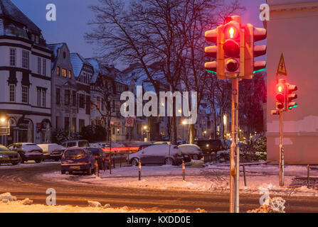 Snow-covered traffic lights,red,pedestrian lights,evening twilight,old Bremen houses,Bremen,Germany - Stock Photo