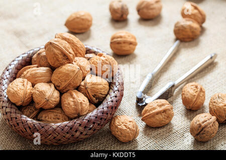 Walnuts in a small basket on a table - Stock Photo