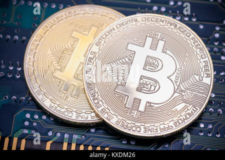Symbol image digital currency, silver physical coins Bitcoin on printed circuit board - Stock Photo
