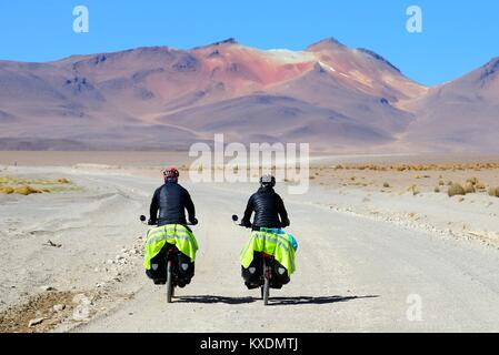 Two cyclists with luggage ride on the runway of the lagoon route, Reserva Nacional de Fauna Andina Eduardo Abaroa, - Stock Photo