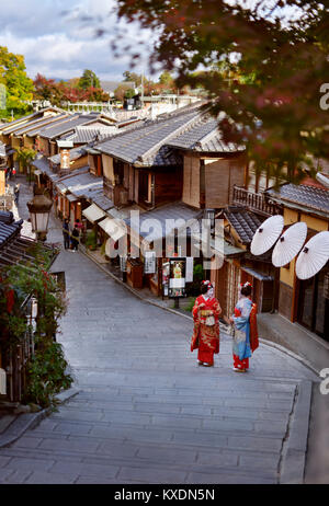 Two Maiko, Geisha apprentices in colorful kimono standing on an old street Yasaka dori in Kyoto, near Kiyomizu-dera, - Stock Photo