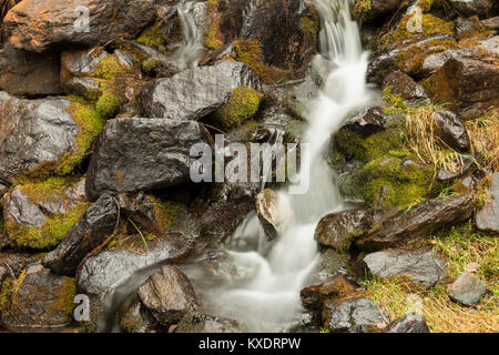 Small waterfall between rocks and moss, Aosta Valley, Italy
