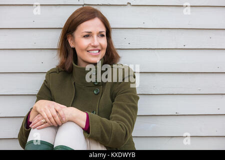 Portrait shot of an attractive, successful and happy middle aged woman female outside smiling - Stock Photo