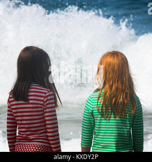 Two Girls Look At the Sea with Big Waves - Stock Photo