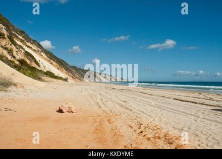 The golden sands of 75 mile beach extending into the horizon with sandbank, sea and blue sky
