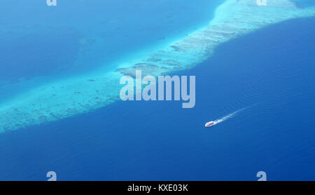Tourist ferry boat running along a coral reef barrier in one of Maldives' atoll. The water is beautifully in deep - Stock Photo