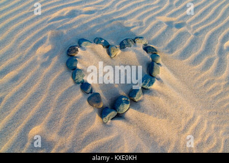 Love heart shape made from stones in the sand - Stock Photo