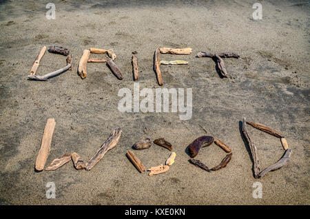 The words Drift Wood spelt out on the beach using driftwood - Stock Photo