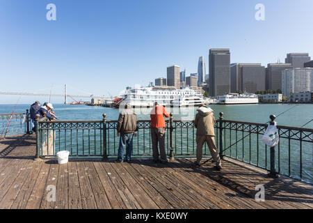 San Francisco, USA - July 2 2017: People fishing on an pier at the Embarcadero in downtown San Francisco with the - Stock Photo