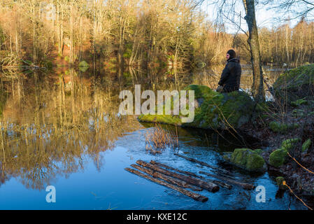 Morning sunshine warming up the river landscape. Ice sheet and debris close to the shore. Moss covered boulders - Stock Photo