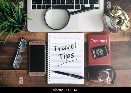 laptop, notebook, smartphone, passport, compass, magnifying glass and clock with TRAVEL TIPS word on wooden table. - Stock Photo