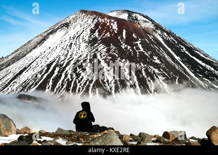 Resting hiker, climber, tramper on the top of the mountain in front of volcano - Stock Photo