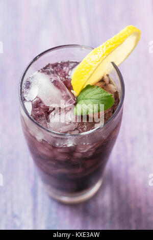 Long drink with elderberry and redcurrant vodka, elderberry syrup, sparkling water and lime juice - Stock Photo
