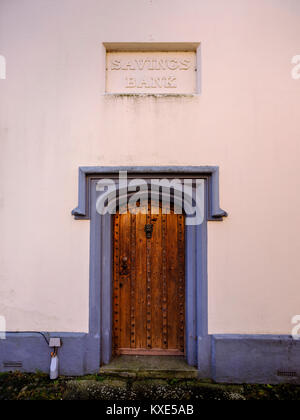 Formerly a bank this now pink house displays the  sign 'Savings Bank' sign above a large ornate wooden door. - Stock Photo