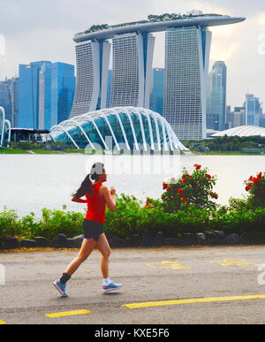 SINGAPORE - FEB 16, 2017: Beautiful young chinese woman running in Singapore bay at sunset. Motion blur. - Stock Photo