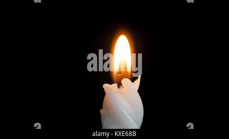 White long candle on black background. Single candle flame light. Long flame, old candle. White candle, black background. - Stock Photo