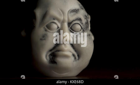 White statuette of stressed, aggressive, frustrated face. Closeup of statuette, figurine of the head of a young - Stock Photo