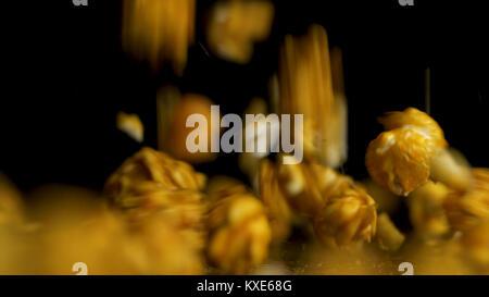 Falling pop corn on black background. Popcorn falls isolted on black background. Pouring popcorn on dark background - Stock Photo