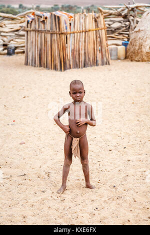 Small child of the Himba tribe people indigenous to the Kunene Region of northern Namibia, south-west Africa standing - Stock Photo