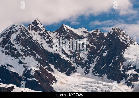 Closeup of towering sharp mountain peaks with glacier ice caps. - Stock Photo