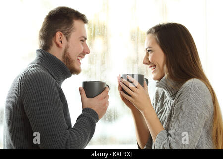Side view portrait of a happy couple in love looking each other in a rainy day of winter at home - Stock Photo