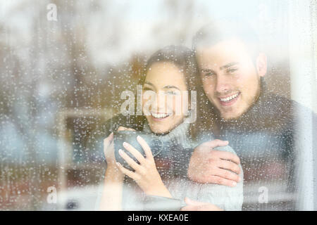 Front view portrait of a positive couple looking outdoors through a window in a rainy day of winter at home - Stock Photo
