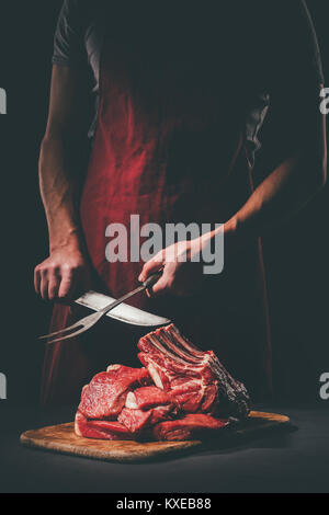 butcher sharpening knife to cut raw meat on wooden cutting board - Stock Photo