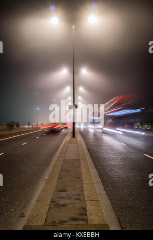 Traffic moves during a long exposure on a dark misty Waterloo Bridge - Stock Photo