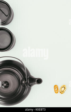 top view of chinese teapot with mugs and gold ingots isolated on white - Stock Photo
