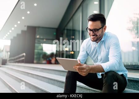 Happy and confident businessman using tablet - Stock Photo