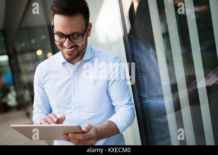 Portrait of businessman in glasses holding tablet - Stock Photo