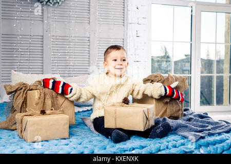 little funny playful boy a child sits on a bed on Christmas day with gift boxes in white wool knitted sweater and - Stock Photo