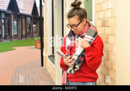 The Asian girl stands at low, beautiful buildings and looks at the book in her hands. She is in the glasses wrapped - Stock Photo