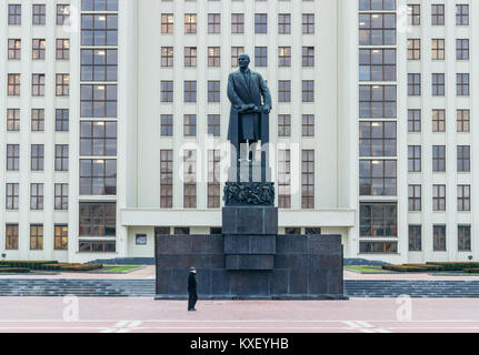 Man walking across the Independence Square, in front of the Lenin monument with the House of Government as background. Minsk, Belarus.