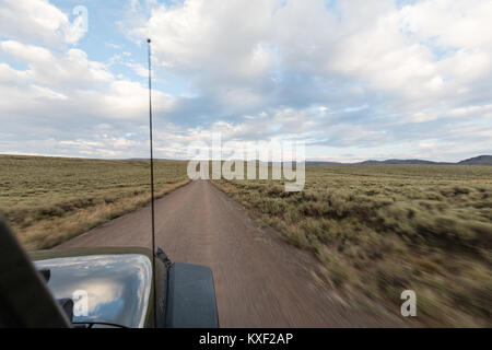 A Jeep drives down a dirt road ready for adventure in Steens Mountain, Oregon. - Stock Photo