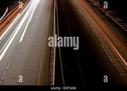Looking down from a passover at the light trails of cars travelling beneath on the Pacific Coast Highway near Santa - Stock Photo