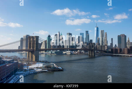 The Brooklyn Bridge and Lower Manhattan skyline seen from the Brooklyn side of the East River in winter - Stock Photo