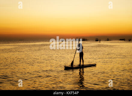 Silhouette of a girl floating on on the sup surfboard at amazing orange sunset over the sea at Boracay island Philippines - Stock Photo