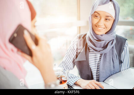 Muslim Woman On Break Using Mobile Phone In cafe - Stock Photo