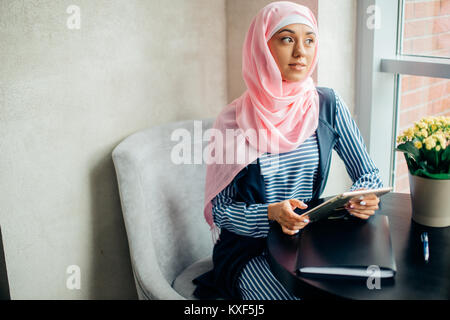 female Muslim college student using tablet computer in cafe - Stock Photo