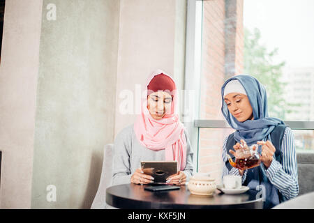 female Muslim college student using tablet computer in cafe