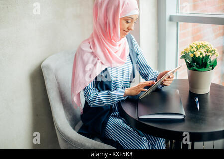 pretty muslim woman use tablet in cafe - Stock Photo