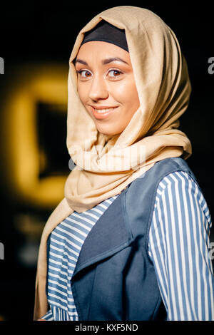 Portrait of a beautiful Muslim woman in cafe - Stock Photo