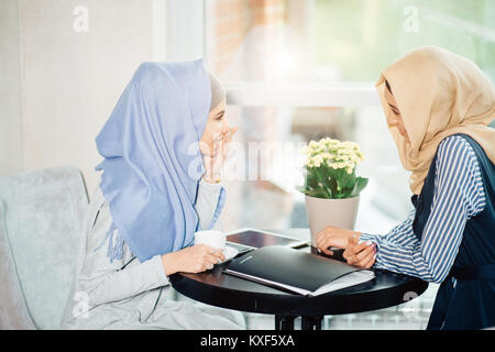 portrait of two woman talking while sitting on couch enjoying coffee - Stock Photo
